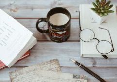 blogger outreach flatlay with mug, notebook and books