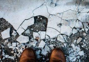 Man's feet infront of broken pieces to find broken links